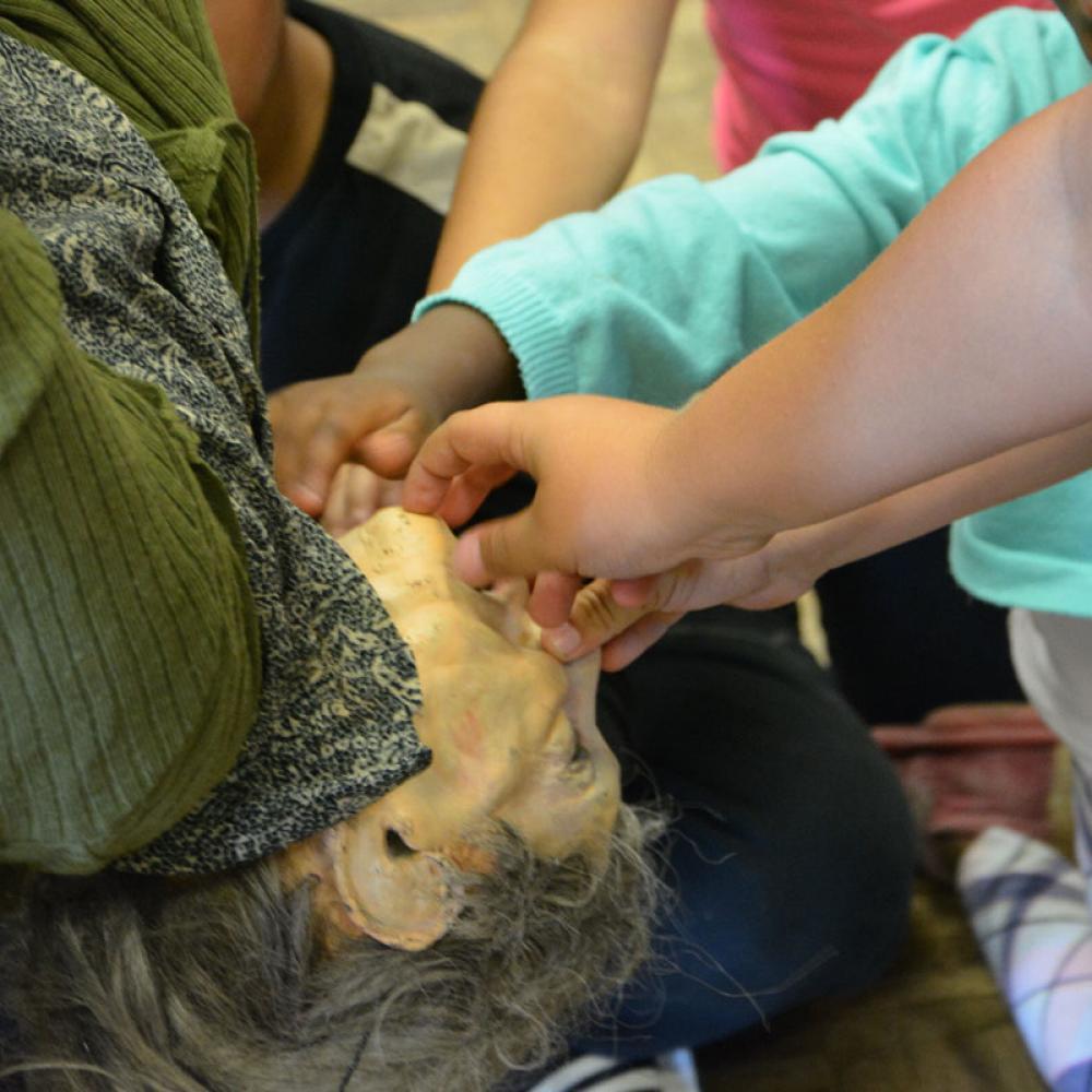 Les enfants, partagés entre peur et fascination, veulent toucher la marionnette pour vérifier qu'elle n'est pas vivante.